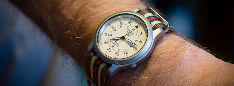 A wrist with an analog watch on it